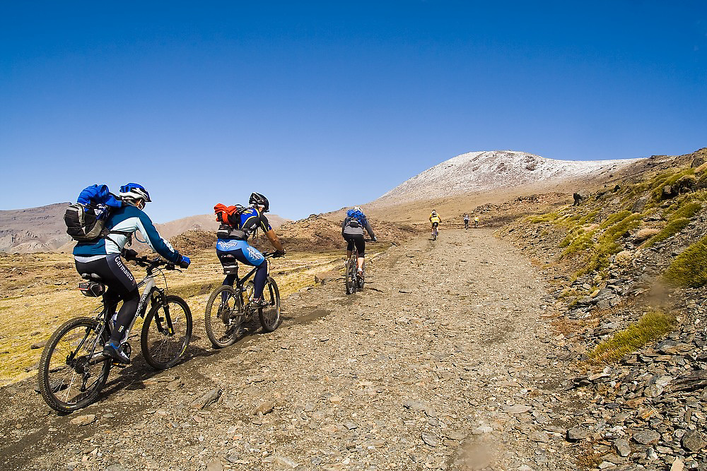 Mountain bikers ride the trail to Mulhacen, visible dusted in snow in the distance, in Sierra Nevada National Park, Andalusia, Spain. Mulhacen is the highest mountain in continental Spain and in the Iberian Peninsula.