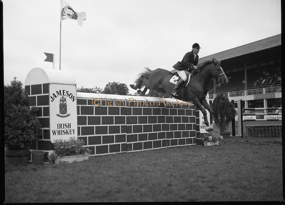 Jameson Whiskey International at the Dublin Horse Show.  (R39).1986..07.08.1986..08.07.1986..7th August 1986..The Jameson Whiskey International at the Dublin Horse Show in the RDS was won by Peter Charles of Great Britain. He rode 'Merrimandias' to victory in the event...Image showsEddie Macken in the Jameson Whiskey International clearing the wall aboard his mount 'Carrolls Flight' at the Horse Show, Jameson's, Irish, Whiskey, jameson,