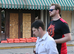 Local residents Ian Campbell, left, and James Quinn pass by a boarded-up, sand-bagged store along River Street on Friday, Sept. 8, 2017, in Savannah, Ga. The city is under mandatory evacuation by Saturday. Photo byCurtis Compton/Atlanta Journal-Constitution/TNS/ABACAPRESS.COM