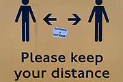 A Covid deniers sticker is central to a Coronavirus sign telling travellers to stay apart on a public transport Please Your Distance bus shelter sign, on 20th January 2021, in London, England.