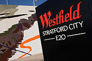 A mural of a tiled artwork and boundary sign of the Westfield City shopping centre in Stratford, home of the 2012 Olympics. Situated on the perimeter fringe of the Olympic Park, Westfield hosted its first day to thousands of shoppers eager to see Europe's largest urban shopping centre. The £1.45bn complex houses more than 300 shops, 70 restaurants, a 14-screen cinema, three hotels, a bowling alley and the UK's largest casino. It will provide the main access to the Olympic park for the 2012 Games and a central 'street' will give 75% of Olympic visitors access to the main stadium so retail space and so far 95% of the centre has been let. It is claimed that up to 8,500 permanent jobs will be created by the retail sector.