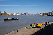 People with canoes on the shoreline of the River Thames at Greenwich on 17th April 2021 in London, United Kingdom.