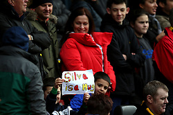 A young fan in the signs holds up a sign reading 'Silva is a mug' during the Premier League match at Vicarage Road, Watford.
