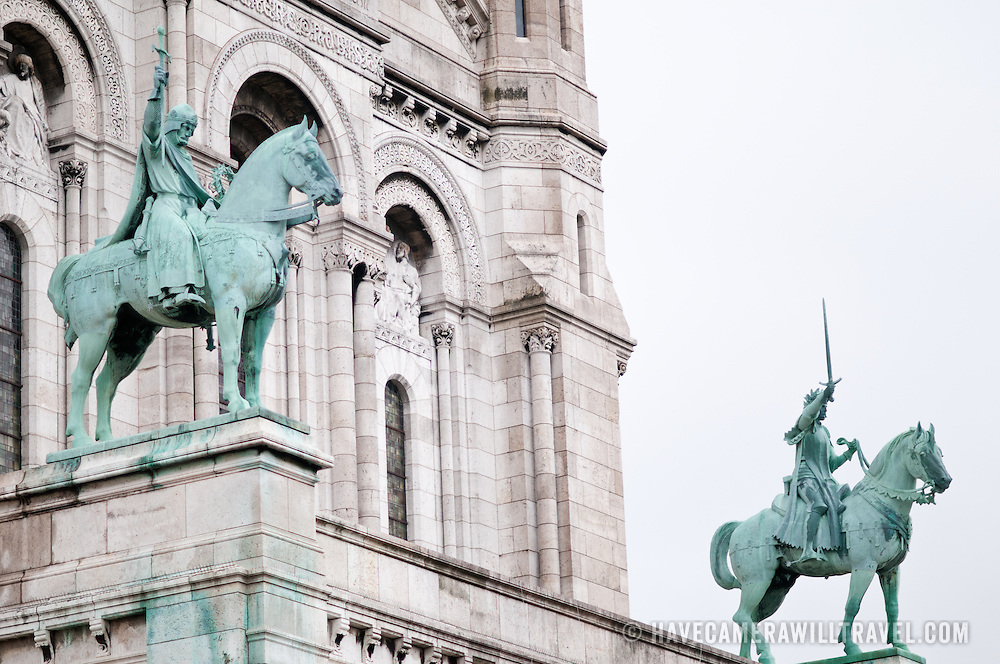 Statues of knights on horses on Sacre Coeur Cathedral in Paris.