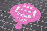 Social distancing signs on the pavement on Gerrard Street as Chinatown remains very quiet with a few people visiting Chinese restaurants to pick up food and to see the red lanterns on 25th June 2020 in London, England, United Kingdom. As the July deadline approaces and government will relax its lockdown rules further, the West End remains quiet, while some non-essential shops are allowed to open with individual shops setting up social distancing systems.