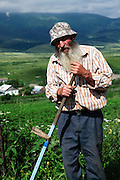 Farmer works in a field with a scythe. Photographed in Armenia