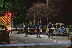 © Licensed to London News Pictures. 31/05/2021. London, UK. Police carry lighting equipment at the crime scene at Montrose Park, Edgware following the fatal stabbing of an 18-year-old male. Metropolitan Police were called at 17:54 BST on Monday 31/05/2021 following reports of a group of males fighting. The man was found suffering from a stab injury in a tennis court area. He was treated by London's Air Ambulance and London Ambulance Service at the scene but was pronounced dead at 19:19 BST. Photo credit: Peter Manning/LNP