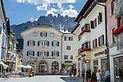 Shoppers gather at at a Despar grocery store in downtown Innichen/San Candido, in the valley of Alta Pusteria (Pustertal), beneath the Sesto Dolomites (Dolomiti di Sesto / Sexten / Sextner / Sextener Dolomiten) mountains, in the Trentino-Alto Adige/Südtirol (South Tyrol) region of Italy, Europe. The Dolomites are part of the Southern Limestone Alps. UNESCO honored the Dolomites as a natural World Heritage Site in 2009.