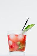 A refreshing strawberry, basil cocktail with a basil garnish.