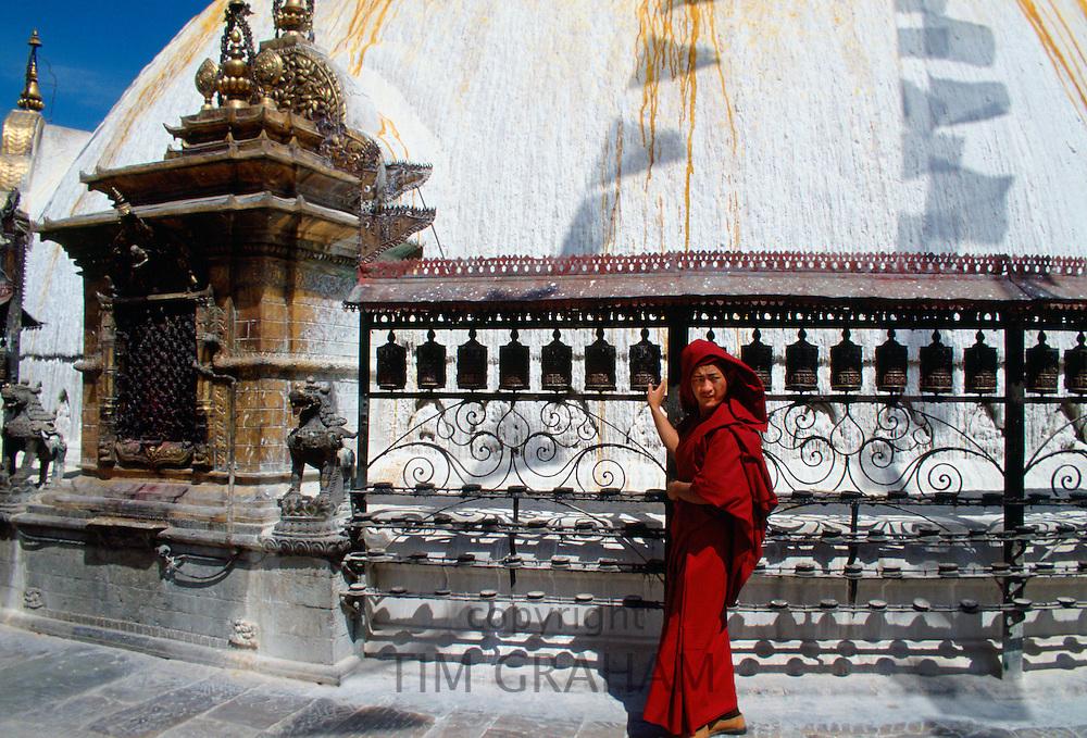 Buddhist worshipper with prayer wheels at Swayambhunath Stupa, Kathmandu Valley, Nepal.