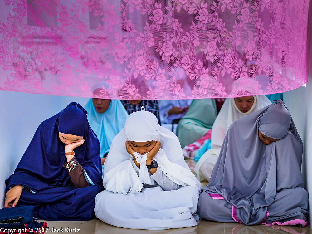 25 JUNE 2017 - BANGKOK, THAILAND: Women participate in Eid al-Fitr prayers at Bang Luang Mosque. Eid al-Fitr is also called Feast of Breaking the Fast, the Sugar Feast, Bayram (Bajram), the Sweet Festival or Hari Raya Puasa and the Lesser Eid. It is an important Muslim religious holiday that marks the end of Ramadan, the Islamic holy month of fasting. Muslims are not allowed to fast on Eid. The holiday celebrates the conclusion of the 29 or 30 days of dawn-to-sunset fasting Muslims do during the month of Ramadan. Islam is the second largest religion in Thailand. Government sources say about 5% of Thais are Muslim, many in the Muslim community say the number is closer to 10%.    PHOTO BY JACK KURTZ
