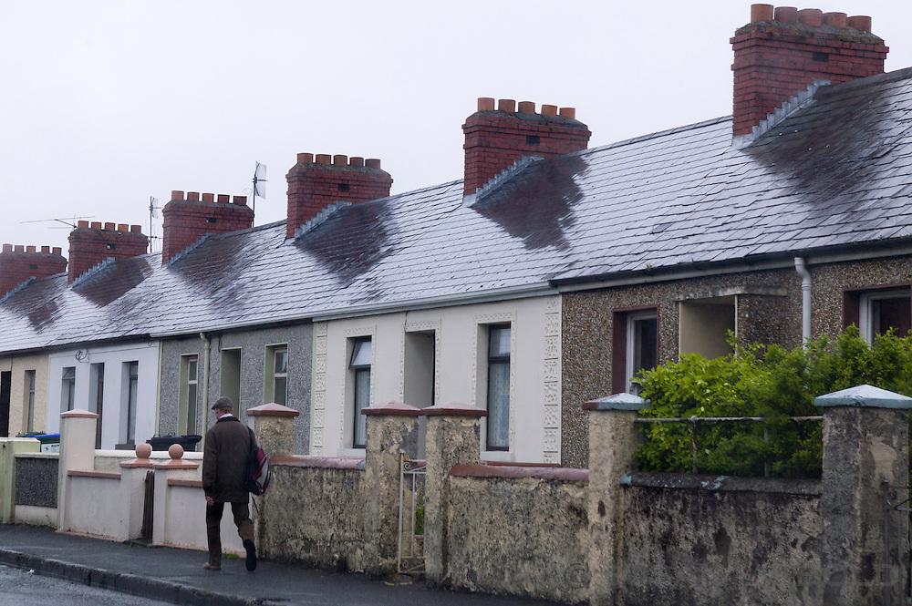 Man walking down street along a row of houses in Ennis, Ireland.