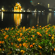 Turtle Tower (also known as Tortoise Tower on a small island in Hoan Kiem Lake in the historical center of Hanoi, Vietnam. In the foreground is a garden of bright flowers.