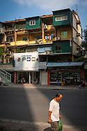 Man momentarily illuminated by a stream of light as he walks along Pham Ngoc Thach street, Hanoi, Vietnam, Southeast Asia