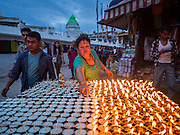 31 JULY 2015 - KATHMANDU, NEPAL: A woman sets out butter lamps during the full moon procession around the Bodhnath Stupa. Bodhnath Stupa in the Bouda section of Kathmandu is one of the most revered and oldest Buddhist stupas in Nepal. The area has emerged as the center of the Tibetan refugee community in Kathmandu. On full moon nights thousands of Nepali and Tibetan Buddhists come to the stupa and participate in processions around the stupa. The stupa was heavily damaged in the earthquake of 25 April 2015 and people are no longer allowed to climb on the stupa, now they walk around the base and pray with butter lamps.   PHOTO BY JACK KURTZ