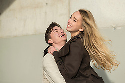 Young man lifting up his girlfriend and smiling, Munich, Bavaria, Germany