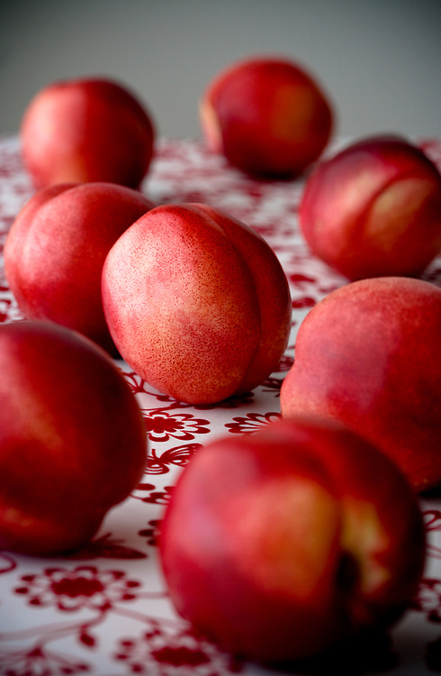Fresh red nectarines on a red pattern surface