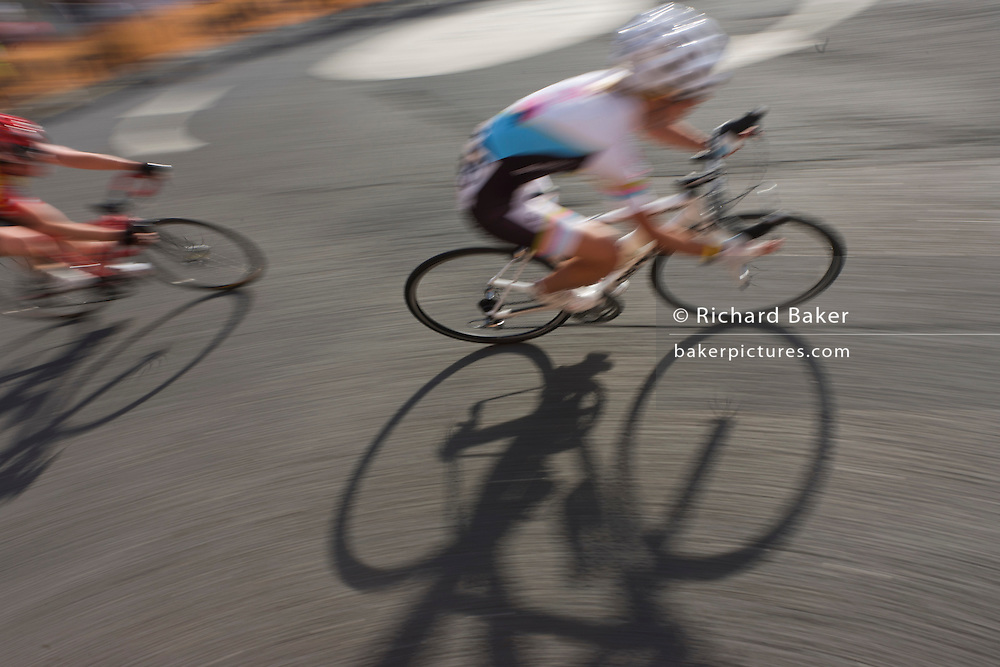 With bike shadows, blurred women cyclists turn into a corner of a Woking street during the Halfords 2011 Tour series.