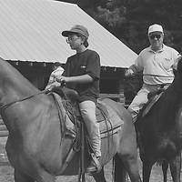 1. When was this photo taken?<br /> <br /> 1992<br /> <br /> 2. Where was this photo taken?<br /> <br /> At a horseback riding resort in upstate New York<br /> <br /> 3. Who took this photo?<br /> <br /> Nancy Kaye<br /> <br /> 4. What are we looking at here?<br /> <br /> My nephew Matthew, as an adolescent, and his grandfather Sam (my father), sharing a horseback riding experience at a family reunion in upstate New York.<br /> <br /> 5. How does this old photo make you feel?<br /> <br /> This image evokes in me a mixture of longing and bittersweet feelings. My nephew Matthew was very close with his grandfather, who passed away only seven years after this photo was taken. The loss was extremely difficult for Matthew. He is now a father of 2 boys and named his older son Sam, after his grandfather (and my father). I see in this photo my father as I'd like to remember him--strong and enjoying time with his family.<br /> <br /> 6. Is this what you expected to see?<br /> <br /> No! I had forgotten about these images and the details of this extended family reunion. <br /> <br /> 7. Does this photo bring back any memories?<br /> <br /> Yes, this brings back memories of my father, who so enjoyed his close relationship with Matthew, his first grandchild. I see in this photo the vigorous, optimistic person that my father was. I had no way of knowing at the time that this sort of physical activity would not be possible for him in a few short years.<br /> <br /> 8. How do you think others will respond to this photo? <br /> <br /> I think that people will notice how serious they look and how my father's horse appears to be challenging him. Nevertheless this was a special moment that grandfather and grandson had together, taking pleasure from each other's company.