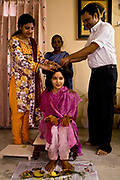 Shweta Singhal begins the preparations and rituals of her three day wedding ceremony in her home in Jaipur, here her forehead is being marked with sandlewood, after it has been smeared in saffron, dried tumeric, and vermillion, her faced is bathed in buttermilk by her family, Rajasthan, India