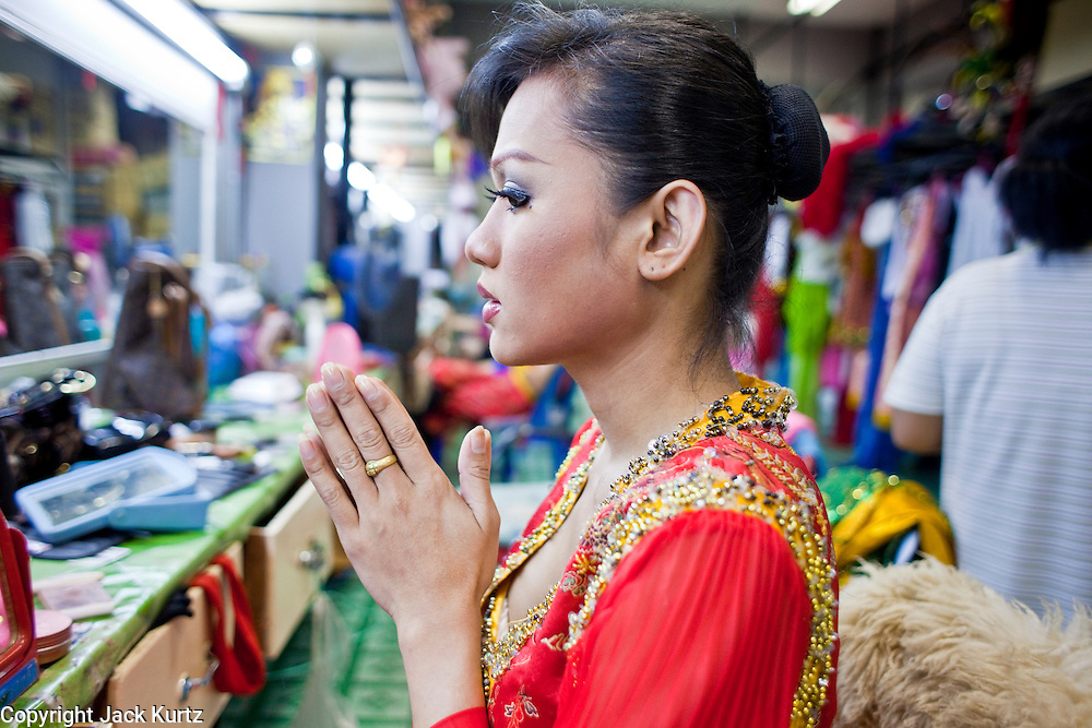 "Oct. 7, 2009 -- BANGKOK, THAILAND:  A ""ladyboy"" says a Buddhist prayer before going on stage at the Mambo Cabaret in Bangkok, Thailand. The performers at the Mambo Cabaret in Bangkok, Thailand are all ""Ladyboys,"" or kathoeys in Thai. Recognized as a third gender, between male and female, they are born biologically male but live their lives as women. Many kathoey realize they are third gender in their early teens, some only as old 12 or 13. Kathoeys frequently undergo gender reassignment surgery to become women. Being a kathoey in Thailand does not carry the same negative connotation that being a transgendered person in the West does. A number of prominent Thai entertainers are kathoeys. Photo by Jack Kurtz / ZUMA Press"