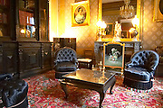 One of the living rooms salons upstairs in the mansion where the Deutz family used to live black upholstered chairs a coffee table a book case paintings on the walls and many other antiques at Champagne Deutz in Ay, Vallee de la Marne, Champagne, Marne, Ardennes, France, low light grainy grain