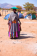 Herero women at a funeral gathering, tents and huts can be seen in the background. Kaokoland, Namibia