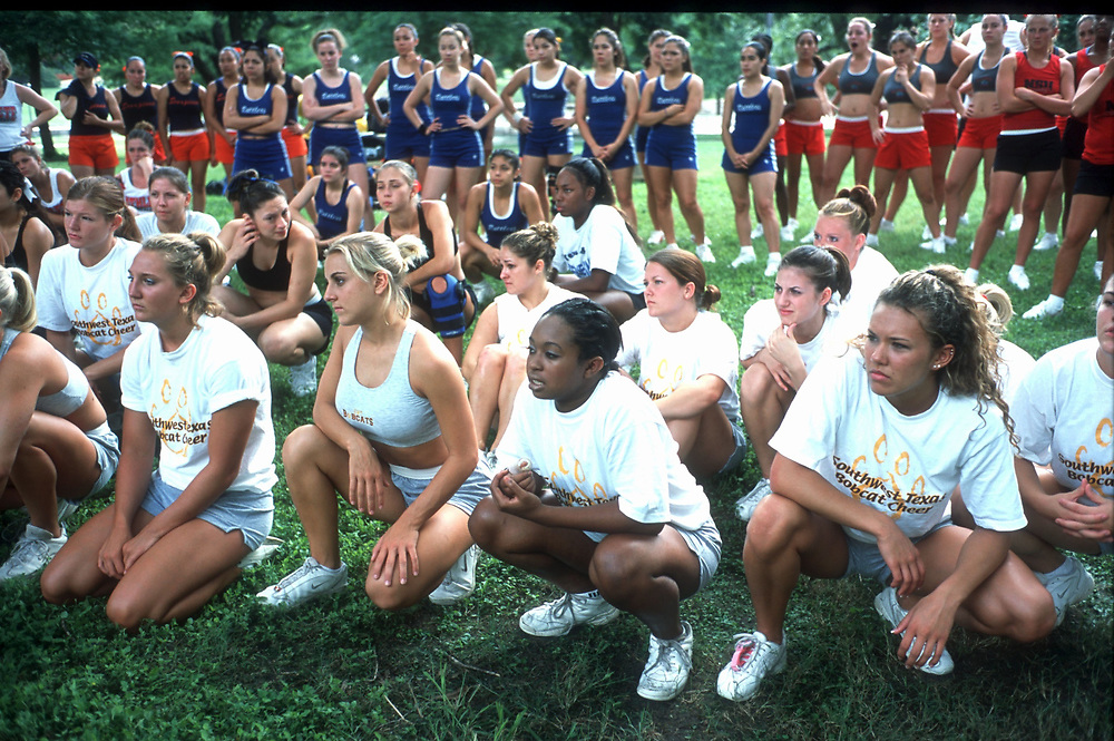 San Marcos, Texas Cheerleaders watch as the Universal Cheerleaders Association teachers demonstrate a stunt at the college camp.  ©Bob Daemmrich /The Image Works