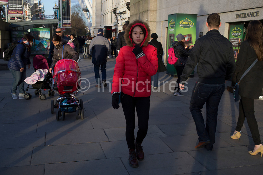 Chinese tourist walking along the Southbank on a cold winter day, wrapped up in a red fur lined parker. London, UK.