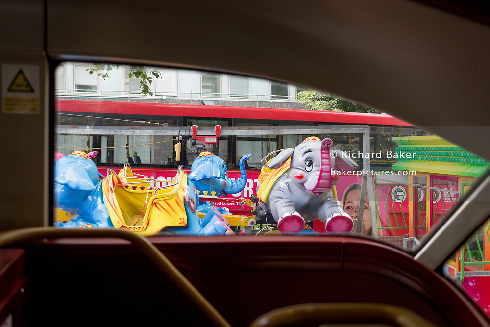 Seen from a London bus are fairground elephants being transported on a lorry through Camberwell, south London, on 19th August 2019, in London, England.