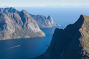 A boat sails alone towards open water in Reinefjorden, Lofoten Islands, Norway.