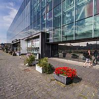 Nederland, Amsterdam, 7 augustus 2017.<br />Oostenburg is een van de drie Oostelijke Eilanden in Amsterdam, die in de tweede helft van de 17e eeuw in het IJ werden aangeplempt. Het ligt tussen het eiland Wittenburg en de Czaar Peterbuurt. De naam van het eiland wordt verklaard door de meest oostelijke ligging ten opzichte van Kattenburg en Wittenburg.<br /> <br /> Het gebied bestaat uit twee delen: het eigenlijke Oostenburg, ook wel Oostenburg-Zuid genoemd, en het Oostenburgereiland. Deze twee voormalige eilanden, beide na demping van delen van de Oostenburgervaart verbonden aan de Czaar Peterbuurt, worden van elkaar gescheiden door de Oostenburger Dwarsvaart en zijn verbonden door een smalle ophaalbrug, bekend als de Werkspoorbrug of Storkbrug.<br /> <br /> Op het Oostenburgereiland op het voormalige terrein van Werkspoor bevinden zich de Theater Fabriek Amsterdam, de Hallen van Stork en INIT-gebouw, een bedrijfsverzamelgebouw waar onder andere de redacties van de dagbladen Het Parool, Trouw en de Volkskrant zijn gevestigd. De woningcorporatie Stadgenoot is eigenaar van het merendeel van de gebouwen en de grond[2].<br /> <br /> Omdat op Oostenburg de bedrijfsbebouwing de grootste oppervlakte inneemt, is er ten opzichte van de omringde buurten relatief minder woningbouw.<br />Oostenburg, een ontwikkeling in jaren<br /> Naast het stedenbouwkundig plan voor de organische ontwikkeling van Oostenburg maakte Urhahn ook het Masterplan Openbare Ruimte. Oostenburg, het voormalige terrein van de VOC en Werkspoor, wordt niet in één keer getransformeerd tot een nieuwe buurt om te wonen en te werken. Er is ruimte voor ontwikkeling door diverse partijen, zodat een rijk pallet aan gebouwen en functies zal verrijzen. De openbare ruimte vormt de tegenhanger van de diversiteit en contrasten in de bebouwing: een samenhangend tapijt dat de beoogde identiteit van het gebied zal benadrukken. Dit masterplan vormt het kader voor de inrichting van de openbare ruimte. Op basis hiervan worde