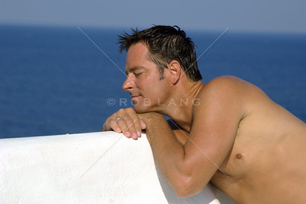 man relaxing by the sea while leaning on a white wall