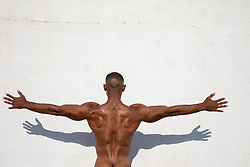 back of a shirtless muscular black man with arms stretched out