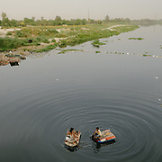 Kids collect and recycle garbage below the Old Iron Bridge, on the polluted Yamuna river.