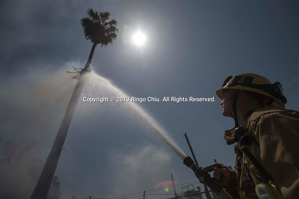 A Los Angeles City firefighter sprays water on a palm tress as a trash fire that occurred Tuesday, April 23, 2013, along the Hollywood (101) Freeway near downtown Los Angeles. (Photo by Ringo Chiu/PHOTOFORMULA.com).