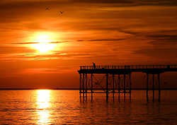 © Licensed to London News Pictures. <br /> 28/08/2017<br /> SALTBURN-BY-THE-SEA, UK.  <br /> A fisherman casts from the end of the pier as the sun rises over Saltburn-by-the-Sea on Bank Holiday Monday.<br />   <br /> Photo credit: Ian Forsyth/LNP