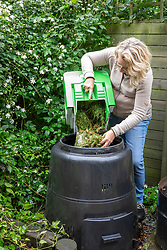Mixing grass clippings with soil when adding to a compost bin.