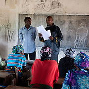 Carers of vulnerable children and EVA staff, Enock Nyakundi, a volunteer from Kenya work on a new constitution for the carer support group in rural Makurdi. EVA provide HCT in three rural communities near Makurdi in Benue state. Benue state has got one of the highest HIV prevalence in Nigeria and EVA aim to target vulnerable children who would otherwise miss out of being tested for HIV and therefor not know their HIV statues.  Education As a Vaccine Against Aids (EVA) in Nigeria.