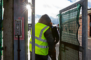A security guard opens the only entrance to access Napier Barracks on the 12th of January 2021, Folkestone Kent. Over 400 asylum seekers are being kept at Napier Barracks in unsuitable, cold accommodation, they are experiencing mental health issues as well as being vulnerable to health conditions including COVID-19.  (photo by Andy Aitchison)