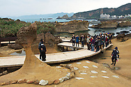 """Tourists line up to have their picture taken in front of """"Queen's Head Rock"""", probably one of Taiwan's most famous sites."""