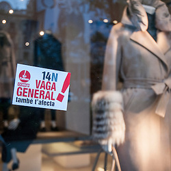 A sticker advertising the general strike is stuck on the window of a department store.