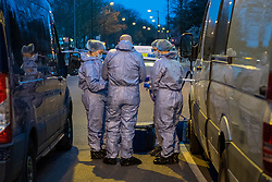 © Licensed to London News Pictures. 09/03/2021. London, UK. Forensic investigators in discussion next to a cordon after Metropolitan Police closed off Poynders Road in what is believed to be connected to the search for missing person Sarah Everard. Photo credit: Peter Manning/LNP