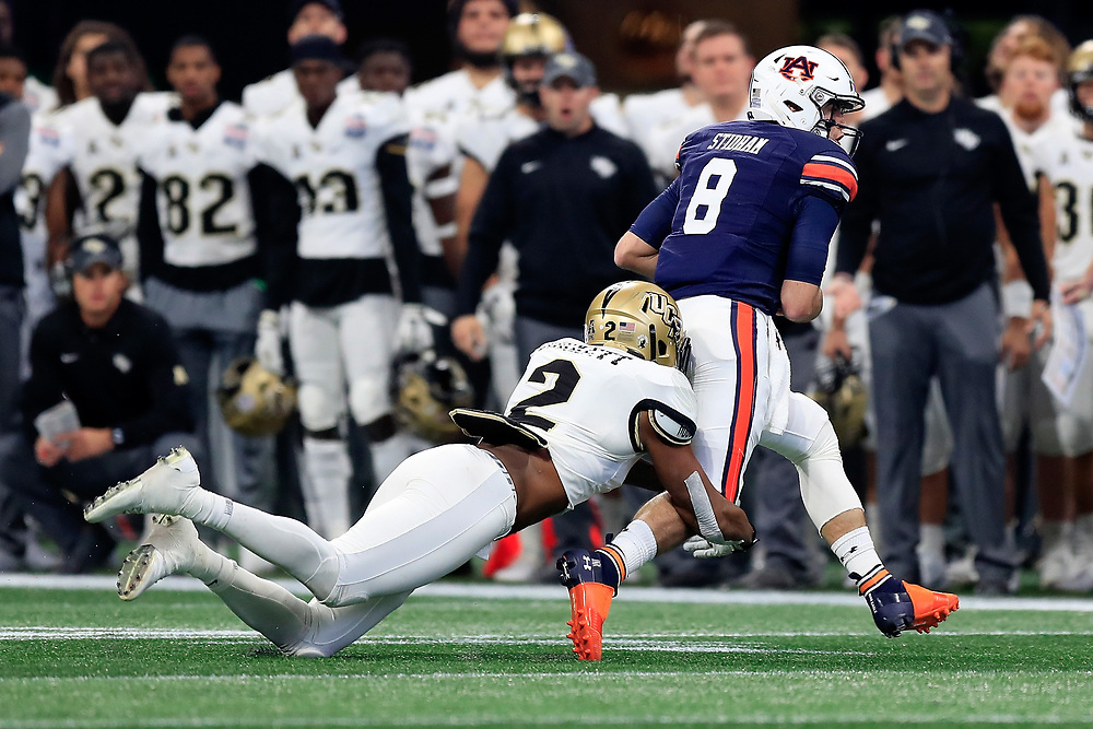 Auburn Tigers quarterback Jarrett Stidham (8) is tackled by UCF Knights linebacker Chequan Burkett (2) during the 2018 Chick-fil-A Peach Bowl NCAA football game on Monday, January 1, 2018 in Atlanta. (Paul Abell / Abell Images for the Chick-fil-A Peach Bowl)