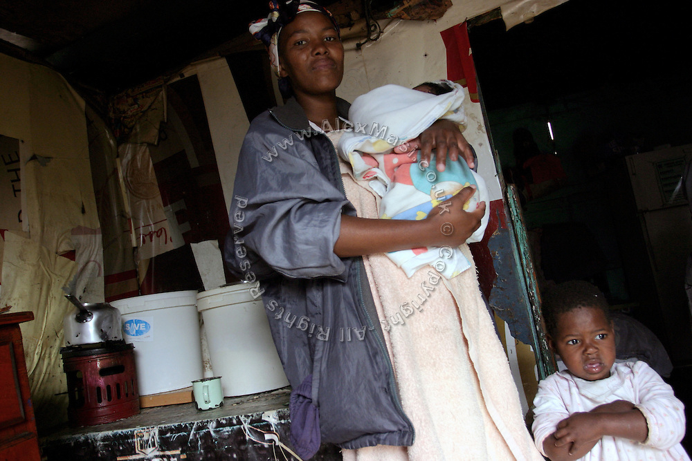 Bulelwa, a HIV+ woman, is standing in her house with Mxolisi, 2, (right) her HIV+ child in the impoverished area of Langa. Bulelwa is holding a new born baby who has not been tested yet.