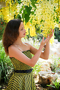 A young female teen of 14, Enjoys the flowers in her garden Model release available