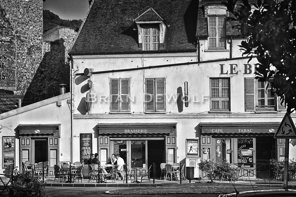 Men seated at an outdoor cafe in Marly, France.  Aspect Ratio 1w x 0.667h