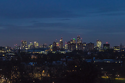 Primrose Hill, London, January 12th 2017. Dawn breaks over London, seen from Primrose Hill, as the South East of England braces itself for rain and possibly snow later in the day. PICTURED: The city skyline, its buildings still lit up, emerges from the darkness.