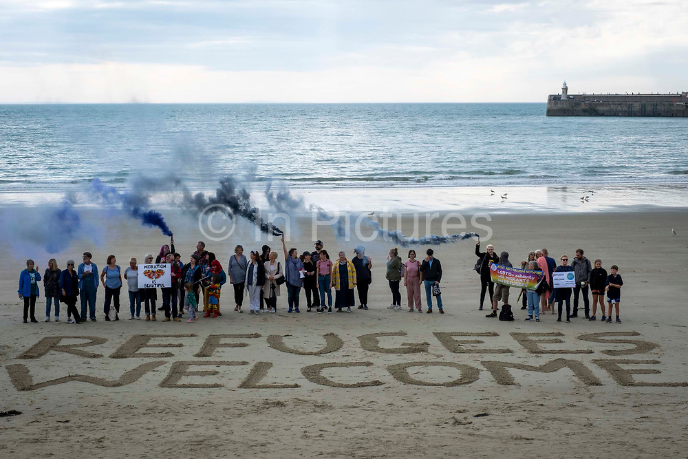 Local residents and members of an Kent's Anti-Racism Network peacefully stand behind 'Refugees Welcome' written in the sand on Sunny Sands Beach, Folkestone, Kent, UK.  This demonstrations was organised in response to reports that members of the far-right group, Britain First, have started patrolling beaches around Dover and Folkestone to try to catch migrants crossing the channel in small boats.