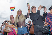 Spectators using mobile phones during the annual Brighton Pride parade on the 3rd August 2019 in Brighton in the United Kingdom.